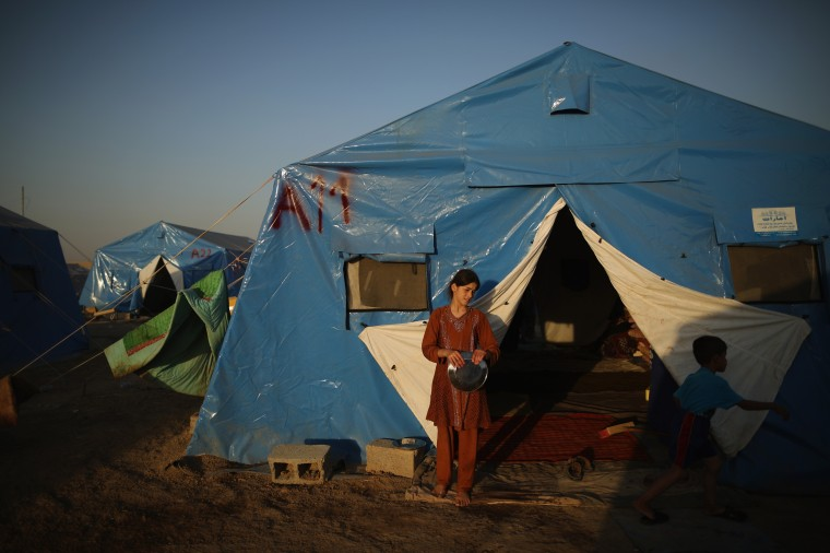 A girl stands outside her tent at a temporary displacement camp near a Kurdish checkpoint in Kalak, Iraq. Thousands of people have fled Iraq's second city of Mosul after it was overrun by ISAS (Islamic State of Iraq and Syria) militants. Many have been temporarily housed at various IDP (internally displaced persons) camps around the region including the area close to Erbil, as they hope to enter the safety of the nearby Kurdish region. (Photo by Dan Kitwood/Getty Images) ORG XMIT: 497173675