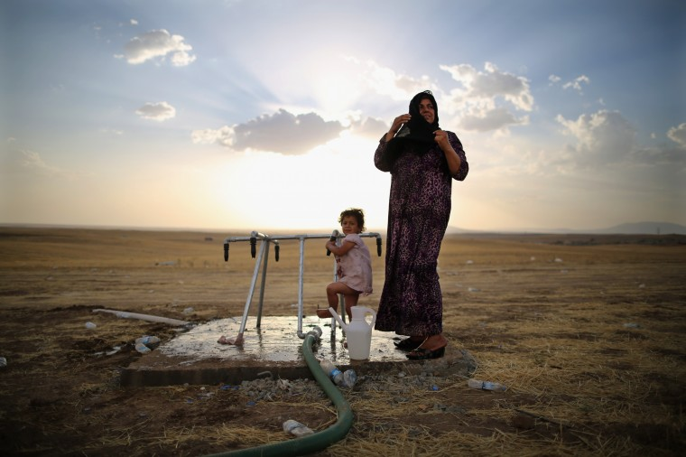 A women and a girl wash at a tap at a temporary displacement camp near a Kurdish checkpoint in Kalak, Iraq. Thousands of people have fled Iraq's second city of Mosul after it was overrun by ISIS (Islamic State of Iraq and Syria) militants. Many have been temporarily housed at various IDP (internally displaced persons) camps around the region including the area close to Erbil, as they hope to enter the safety of the nearby Kurdish region. (Photo by Dan Kitwood/Getty Images) *** BESTPIX *** ORG XMIT: 497173675