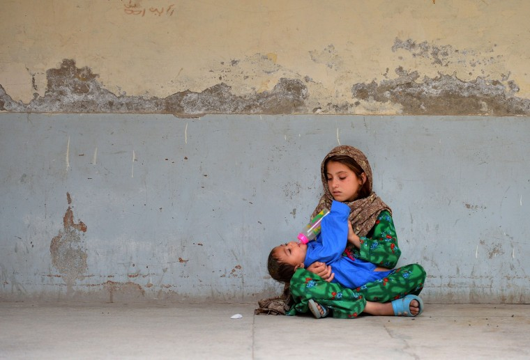 A displaced Pakistani girl from the North Waziristan tribal region gives a drink to a baby at the Women and Children Hospital in Bannu. Pakistani helicopter gunships pounded militant targets in the country's northwest, killing up to 30 rebels as the number of civilians fleeing an expected ground offensive passed 200,000. (A Majeed/AFP-Getty Images)