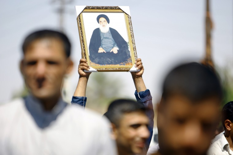 An Iraqi man holds up a portrait of Shiite cleric Grand Ayatollah Ali al-Sistani during a demonstration in the central Shiite Muslim shrine city of Najaf. They gathered to show support for his call to arms to defend the country against the offensive spearheaded by the jihadist Islamic State of Iraq and the Levant (ISIL.) The call came as President Barack Obama said he was exploring all options to save Iraq's security forces from collapse. (Haider Hamdani/AFP-Getty Images)