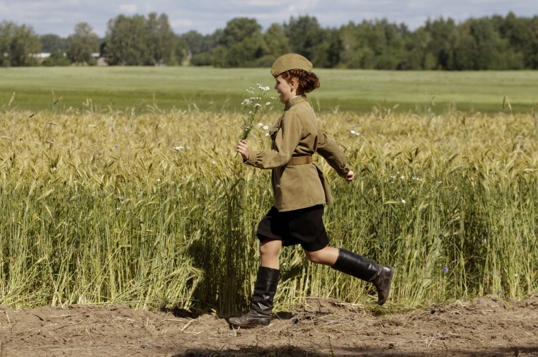 A woman, dressed in World War II costume, runs near the village of Rakovichi, southeast of Minsk. Belarus will mark the 70th anniversary of the country's liberation from the German forces on July 3. (Vasily Fedosenko/Reuters)