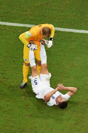 Joe Hart of England helps teammate Gary Cahill stretch during the 2014 FIFA World Cup Brazil Group D match between England and Italy at Arena Amazonia in Manaus, Brazil. (Francois Xavier Marit/Pool/Getty Images)