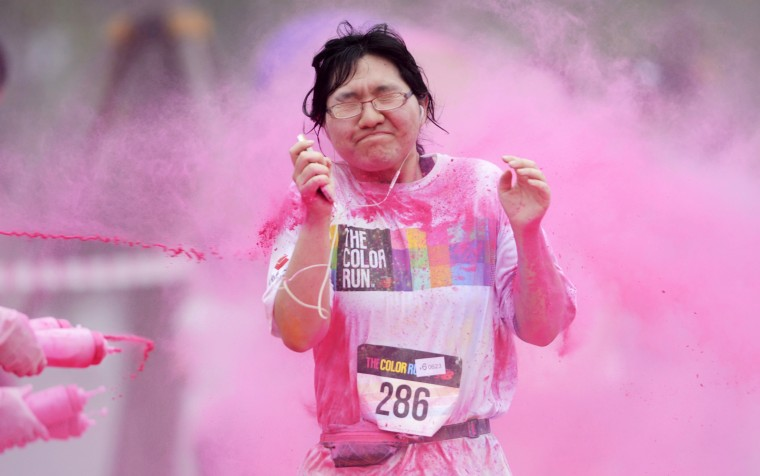 A woman reacts as she is sprayed with colour powder during a five-kilometre colour run event in Beijing, China. (China Daily/via Reuters)