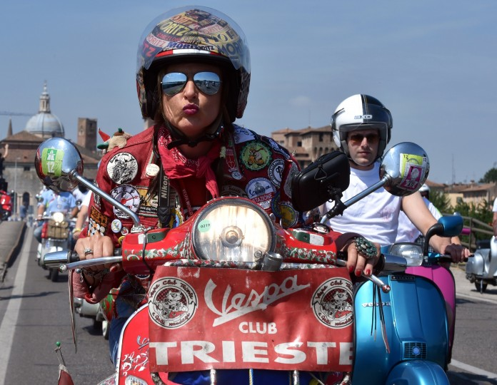 A Vespa club blows kisses in Mantova during Vespa World Days. Vespa lovers from all over Europe and further afield gather together for the largest and best-known rally of its kind worldwide. (Alberto Lingria/AFP-Getty Images)
