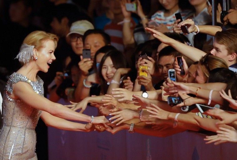 "Australian actress Nicole Kidman shakes hands with fans as she arrives on the red carpet of the Shanghai International Film Festival. Kidman, who is promoting ""Grace of Monaco"" at the festival, received an award for outstanding contribution to film. Shanghai kicked off its annual film festival, a nine-day event with a heavy emphasis on Chinese cinema and a sprinkling of Hollywood stars promoting their latest works. (AFP-Getty Images)"
