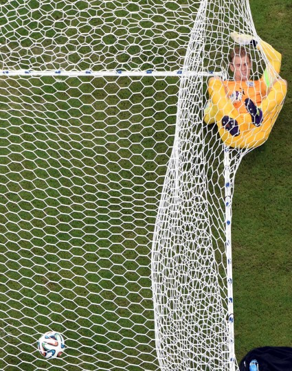 England's goalkeeper Joe Hart lies on the net after Italy's forward Mario Balotelli scored during a Group D football match between England and Italy at the Amazonia Arena in Manaus during the 2014 FIFA World Cup. (Francois Xavier Marit//AFP-Getty Images)
