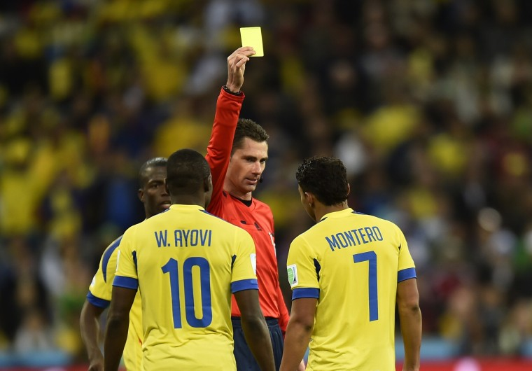 Ecuador's forward Jefferson Montero (R) is shown a yellow card by Australian referee Benjamin Jon Williams during a Group E football match between Honduras and Ecuador at the Baixada Arena in Curitiba during the 2014 FIFA World Cup. (Rodrigo Buendia/AFP-Getty Images)
