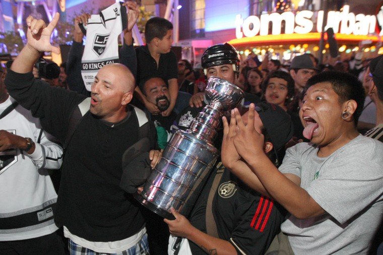 Fans celebrate with an imitation Stanley Cup after the Los Angeles Kings beat the New York Rangers to win the Stanley Cup in Los Angeles, Calif. It is the second time in three years that the Kings have won the Stanley Cup. (David McNew/Getty Images)