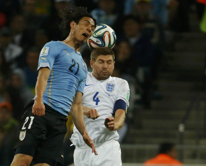 Uruguay's Edinson Cavani (Left) jumps for the ball with England's Steven Gerrard during their 2014 World Cup Group D soccer match at the Corinthians arena in Sao Paulo June 19, 2014. (Laszlo Balogh/Reuters photo)