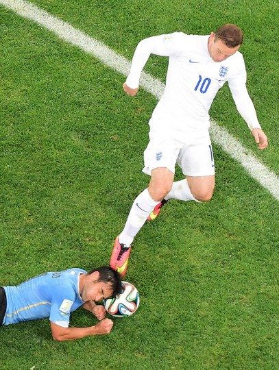 England's forward Wayne Rooney (Right) is tackled by Uruguay's midfielder Nicolas Lodeiro during the Group D football match between Uruguay and England at the Corinthians Arena in Sao Paulo on June 19, 2014, during the 2014 FIFA World Cup. (Francois Xavier Marit/Getty Images)