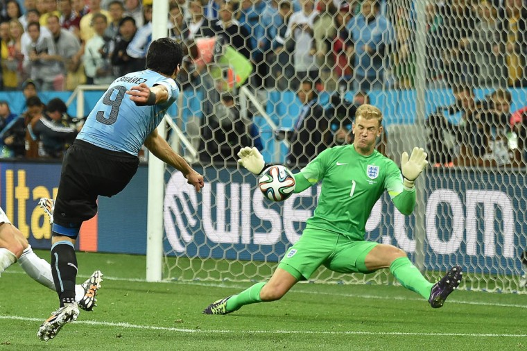 Uruguay's forward Luis Suarez (Left) scores against England's goalkeeper Joe Hart during a Group D football match between Uruguay and England at the Corinthians Arena in Sao Paulo during the 2014 FIFA World Cup on June 19, 2014. (Luis Acosta/Getty Images)