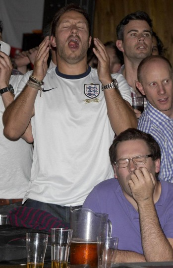 England soccer fans react as their team plays against Uruguay during the 2014 World Cup at a bar in central London June 19, 2014. (Neil Hall/Reuters photo)