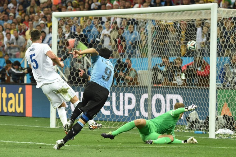 Uruguay's forward Luis Suarez (Center) scores a second goal against England's goalkeeper Joe Hart during a Group D football match between Uruguay and England at the Corinthians Arena in Sao Paulo during the 2014 FIFA World Cup on June 19, 2014. (Luis Acosta/Getty Images)