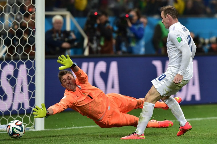 England's forward Wayne Rooney (Right) scores past Uruguay's goalkeeper Fernando Muslera during the Group D football match between Uruguay and England at the Corinthians Arena in Sao Paulo on June 19, 2014, during the 2014 FIFA World Cup. (Nelson Almeida/Getty Images)