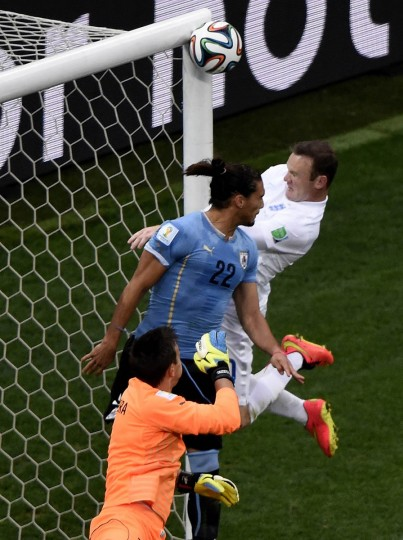 England's forward Wayne Rooney (Right) jumps to head the ball during a Group D football match between Uruguay and England at the Corinthians Arena in Sao Paulo during the 2014 FIFA World Cup on June 19, 2014. (Juan Barreto/Getty Images)