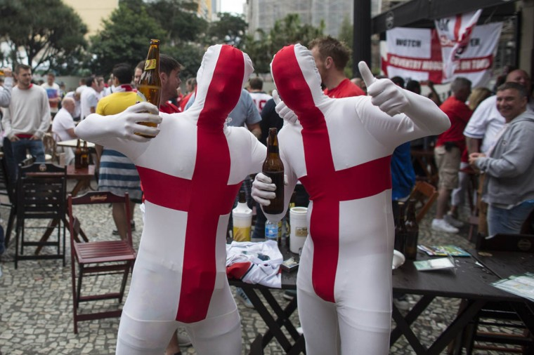 Fans of the England football team wearing full-body suits pose for a photograph in a bar ahead of the England's match against Uruguay on June 19, 2014 in Sao Paulo, Brazil. England are scheduled to play their second group game of the 2014 FIFA World Cup against Uruguay later today. (Oli Scarff/Getty Images)