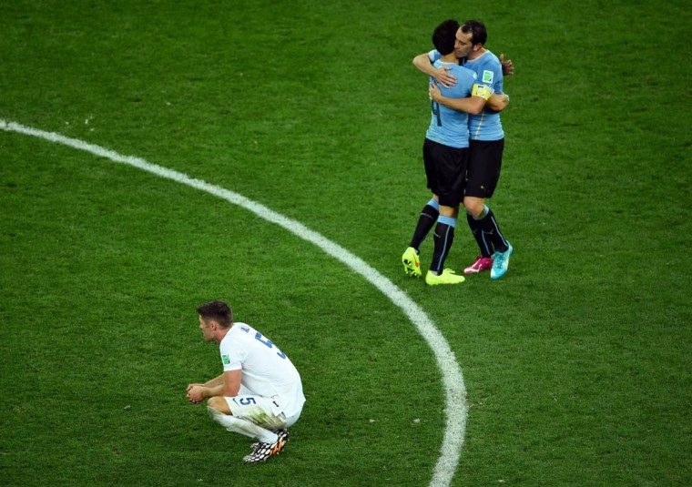 Jorge Fucile and Diego Godin of Uruguay hug as a dejected Gary Cahill of England looks on during the 2014 FIFA World Cup Brazil Group D match between Uruguay and England at Arena de Sao Paulo on June 19, 2014 in Sao Paulo, Brazil. (Matthias Hangst/Getty Images)