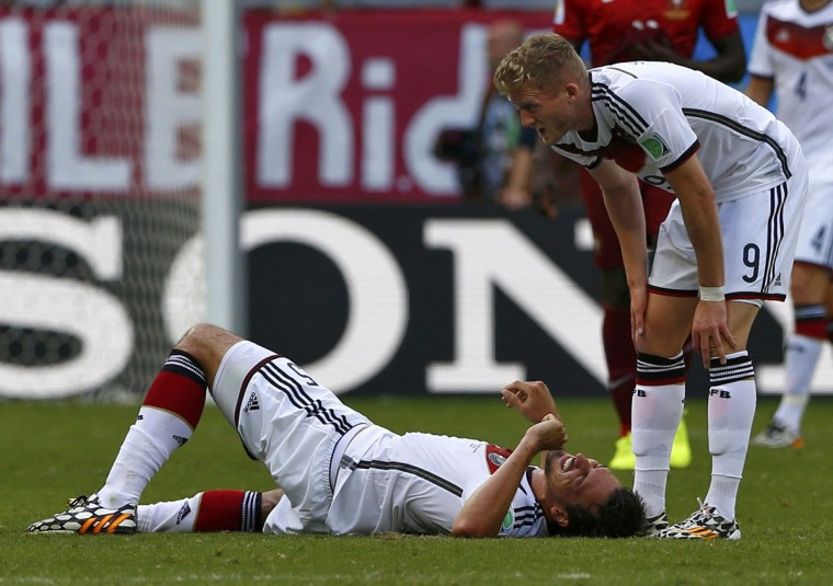 Germany's Andre Schuerrle assists Mats Hummels, who was injured during their 2014 World Cup Group G soccer match against Portugal at the Fonte Nova arena in Salvador on June 16, 2014. (REUTERS/Darren Staples)