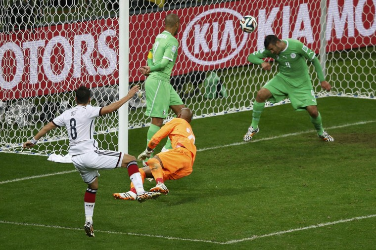 Germany's Mesut Ozil (Left) scores against Algeria during their 2014 World Cup round of 16 game at the Beira Rio stadium in Porto Alegre June 30, 2014. (Leonhard Foeger/Reuters photo)