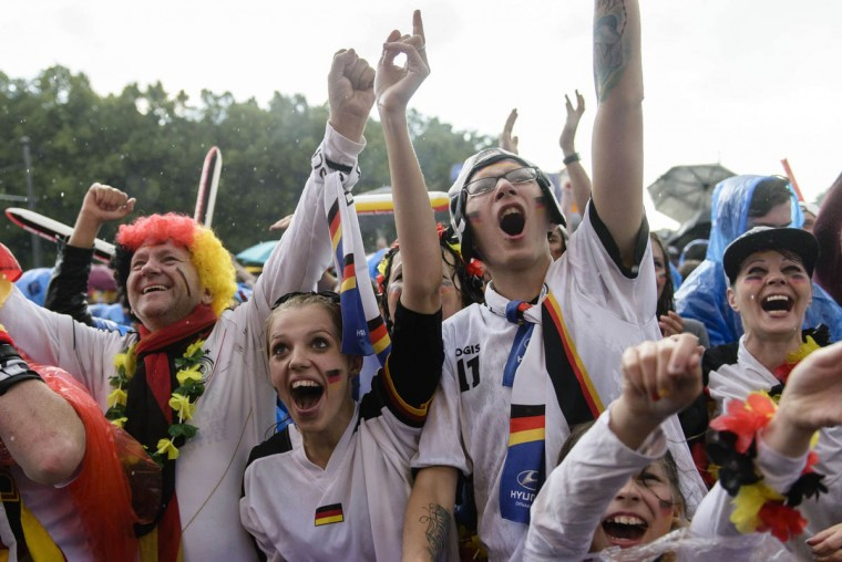 German fans celebrate while they watch the FIFA World Cup 2014 group G football match Germany vs USA in the rain on a giant screen in Berlin, Germany on June 26, 2014. (Clemens Bilan/Getty Images)