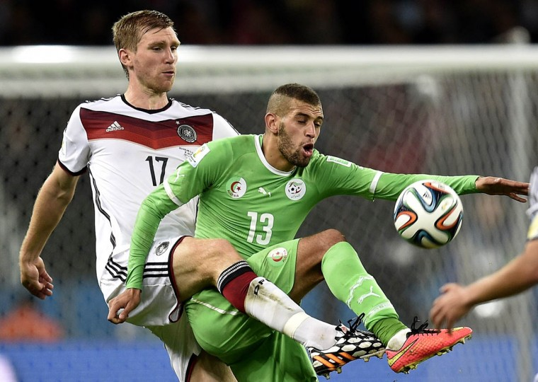 Germany's defender Per Mertesacker (Left) vies with Algeria's forward Islam Slimani during a Round of 16 football match between Germany and Algeria at Beira-Rio Stadium in Porto Alegre during the 2014 FIFA World Cup on June 30, 2014. (Lucas Uebel/Getty Images)