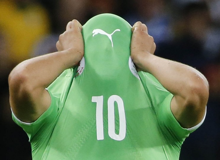Algeria's Sofiane Feghouli covers his face with his jersey as he reacts to his team's loss at the end of their 2014 World Cup round of 16 game against Germany at the Beira Rio stadium in Porto Alegre June 30, 2014. (Edgard Garrido/Reuters photo)