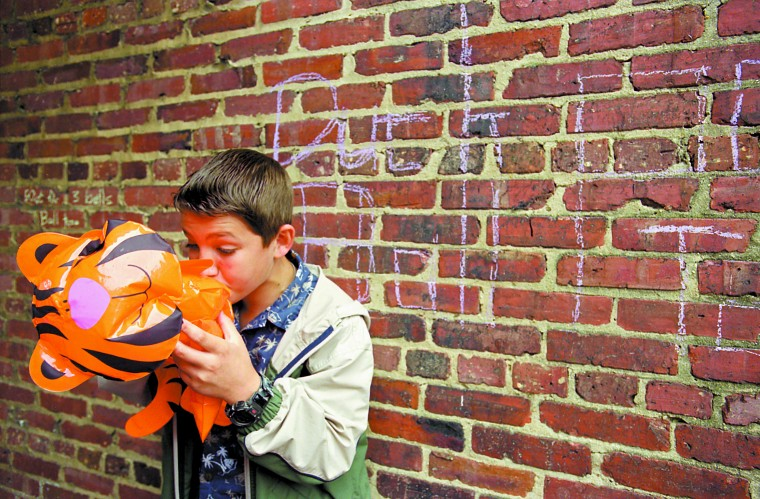 """Andrew Reece, 12, inflates a tiger, one of the prizes for winners of the Ball Toss game he was manning at Saturday's """"Hon Fest"""" at his Aunt Denise's Cafe Hon. (Sun photo, 2001)"""