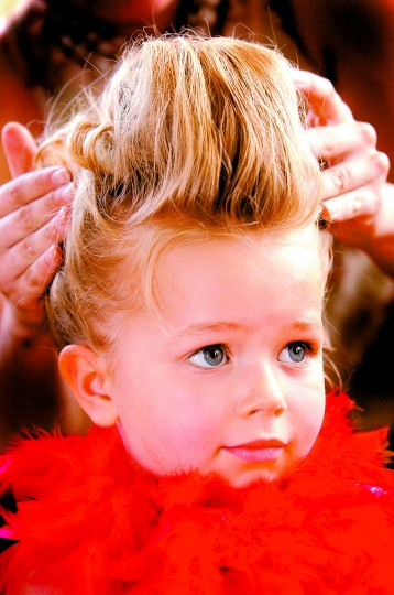 "Four-year-old Maria Graham of Hunt Valley gets her hair coiffed ""hon-style"" by Jenn Nasuta of Hampden prior to the best Hon contest Saturday in Hampden. Although dressed as a ""Hon"" Maria was not eligible to enter the contest, yet she was a crowd favorite on stage. (Sun photo, 2002)"