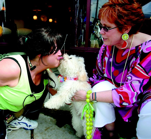 Randy Rom (left), of Mt. Washington and the event director at HonFest, gets a big, wet kiss from her longtime friend Dorothy Wolman's (right) dog Misha. (Staff photo by Lisa Johnson)