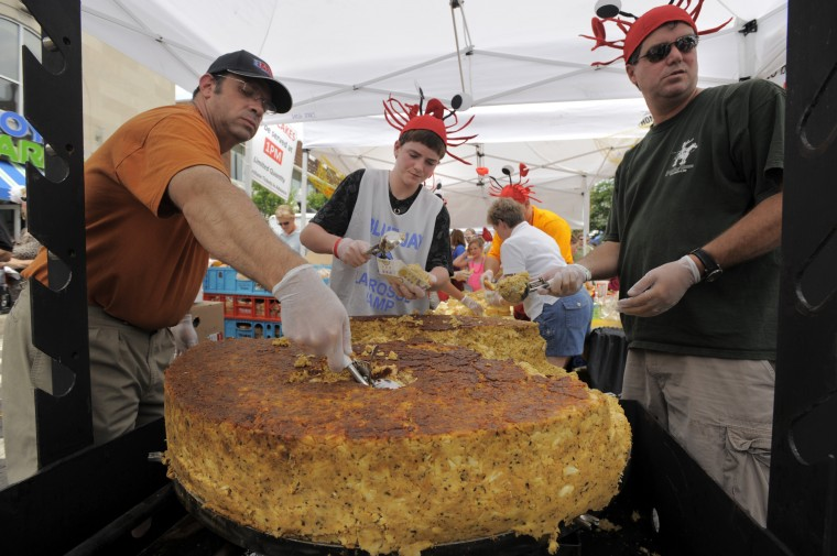 "BALTIMORE, MD -- 06/13/2009 -- Jim Cupp, left, Brendan Schniedwind, 14 and Steve Schwartz work together behind the counter, dipping in to the claimed ""world's biggest crab cake,"" at more than 250 pounds, selling them at $10 each at the annual 2009 Honfest in the Hampden community Saturday, June 13, 2009. (Baltimore Sun Staff/Karl Merton Ferron)"