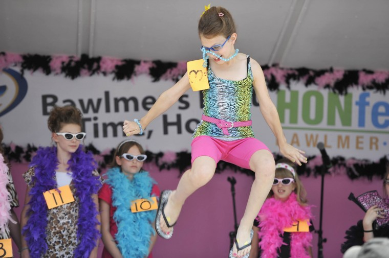 Baltimore, MD--6/9/12--Ali Cataggio, Aberdeen, jumps high in the air when asked to leave the audience with something to remember her by in the final stage of the Miss Honette contest at HonFest in Hampden. (Kim Hairston/Baltimore Sun Staff)