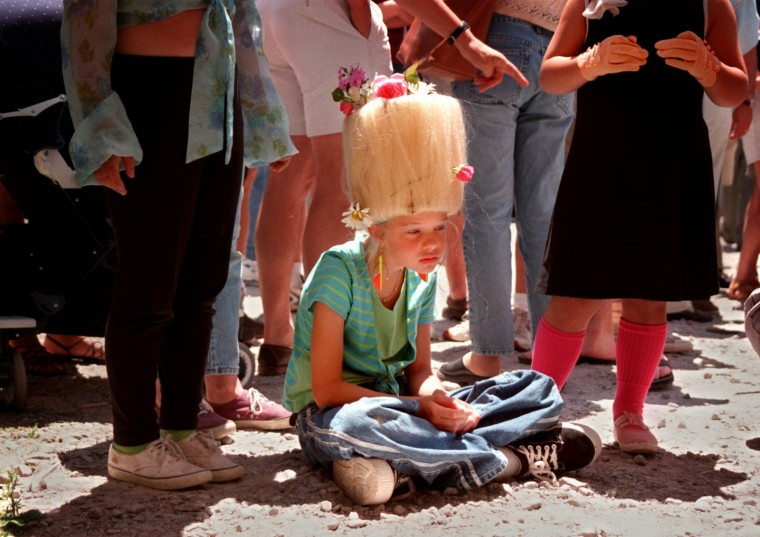 6/6/98--Sarah Huges, 10 (center) waits before she and her cousins go onto the 5th annual Best Hon Contest. They are from Hampden, hon. Sarah's aunt Jane Schock (not in this photo) fixed her hair using a lampshade and wigs. Sarah's grandma coached her and her cousins how to talk and walk like hons, you know. But it was quite hot and her beehive getting heavy, she was tired even before the contest began. (Photo by Chiaki Kawajiri/staff)