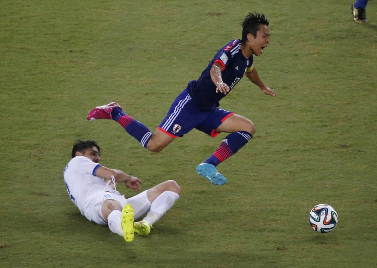 Greece's Kostas Katsouranis fouls Japan's Makoto Hasebe during their 2014 World Cup Group C soccer match at the Dunas arena in Natal June 19, 2014. The foul resulted in a second yellow, which resulted in a sending off for Katsouranis. (Carlos Barria/REuters photo)