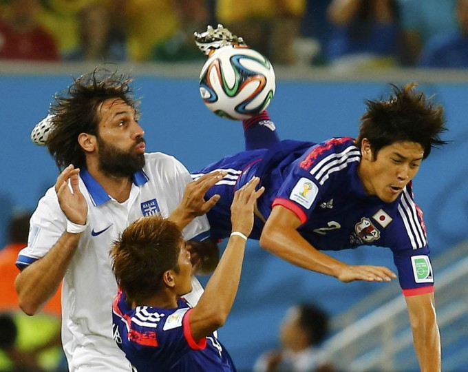Japan's Atsuto Uchida (Right) is fouled by Greece's Giorgios Samaras (Left) during their 2014 World Cup Group C soccer match at the Dunas arena in Natal June 19, 2014. (Kai Pfaffenbach/Reuters photo)