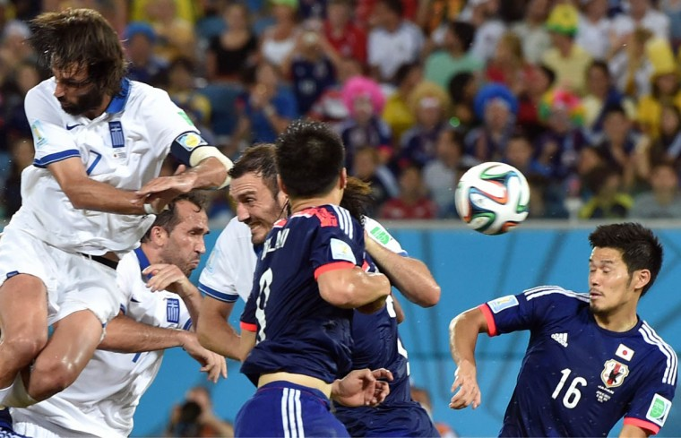 Greece's forward Georgios Samaras (Left) heads the ball during a Group C match between Japan and Greece at the Dunas Arena in Natal during the 2014 FIFA World Cup on June 19, 2014. (Aris Messinis/Getty Images)