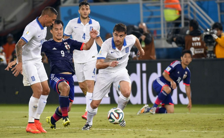 Japan's forward Shinji Okazaki (Center) vies with Greece's defender Sokratis Papastathopoulos (Right) during a Group C football match between Japan and Greece at the Dunas Arena in Natal during the 2014 FIFA World Cup on June 19, 2014. (Fabrice Coffrin/Getty Images)