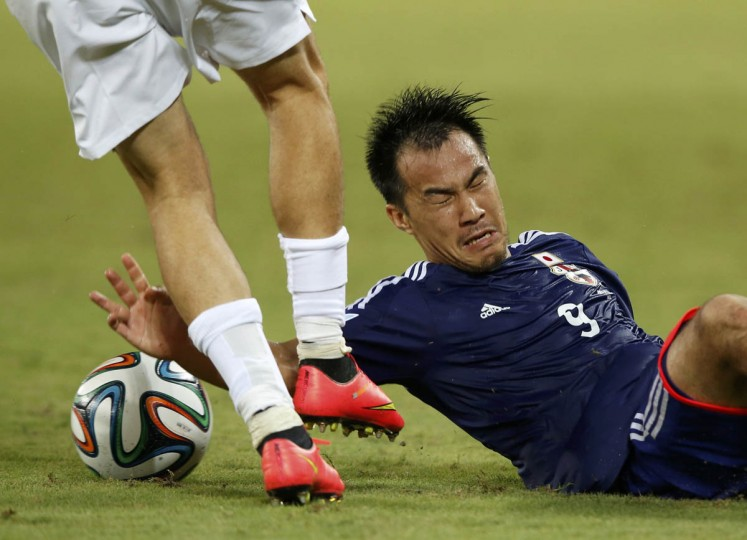 Japan's Shinji Okazaki fights for the ball during their 2014 World Cup Group C soccer match against Greece at the Dunas arena in Natal (Toru Hanai/Reuters photo)