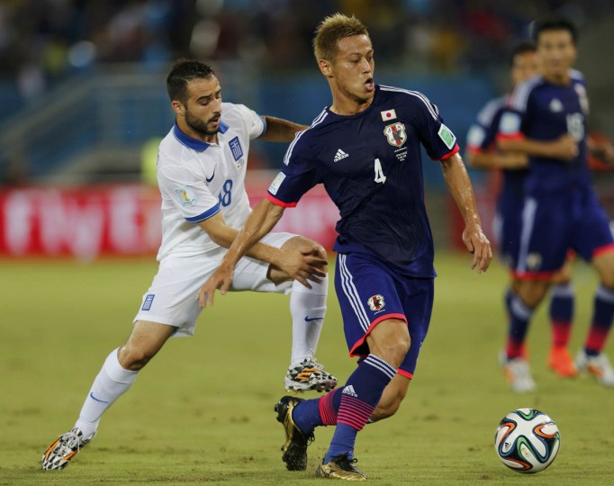 Japan's Keisuke Honda runs for the ball ahead of Greece's Ioannis Fetfatzidis (Left) during their 2014 World Cup Group C soccer match at the Dunas arena in Natal June 19, 2014. (Sergio Moraes/Reuters photo)