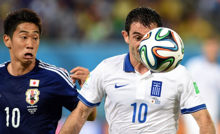 Japan's forward Shinji Kagawa (Left) vies with Greece's midfielder Giorgos Karagounis (Right) during a Group C football match between Japan and Greece at the Dunas Arena in Natal during the 2014 FIFA World Cup on June 19, 2014. (Toshifumi Kitamura/Getty Images)