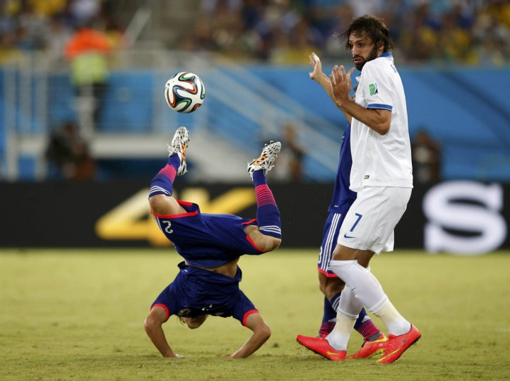 Greece's Giorgios Samaras commits a foul against Japan's Atsuto Uchida (Left) during their 2014 World Cup Group C soccer match at the Dunas arena in Natal June 19, 2014. (Toru Hanai/Reuters photo)