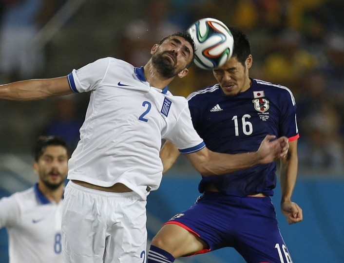 Greece's Giannis Maniatis (2) heads the ball next to Japan's Hotaru Yamaguchi during their 2014 World Cup Group C soccer match at the Dunas arena in Natal June 19, 2014. (Sergio Moraes/Reuters photo)