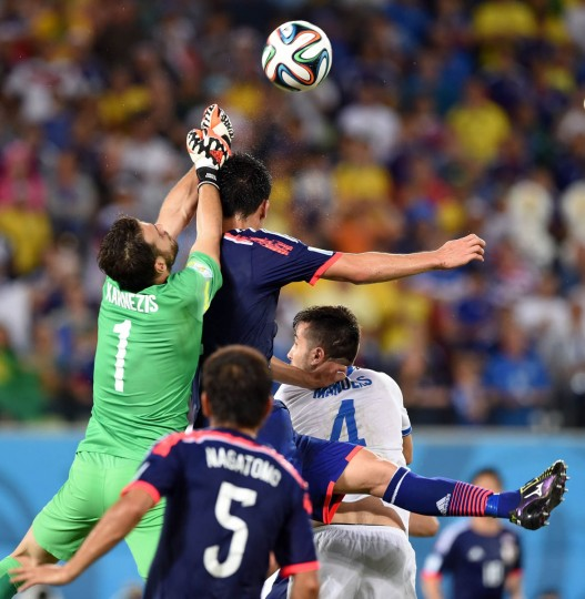 Greece's goalkeeper Orestis Karnezis (Left) jumps for the ball during a Group C football match between Japan and Greece at the Dunas Arena in Natal during the 2014 FIFA World Cup on June 19, 2014. (Toshifumi Kitamura/Getty Images)