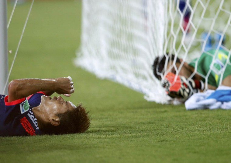 Japan's Yoshito Okubo (Left) lies on the ground after failing to score a goal as Greece's goalkeeper Orestis Karnezis looks on during their 2014 World Cup Group C soccer match at the Dunas arena in Natal June 19, 2014. (Toru Hanai/Reuters photo)