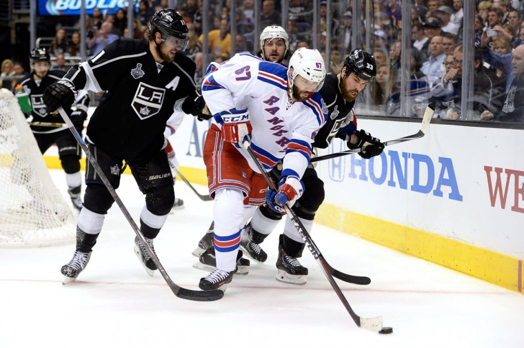 Benoit Pouliot #67 of the New York Rangers with the puck against Anze Kopitar #11 and Willie Mitchell #33 of the Los Angeles Kings in the third period during Game Five of the 2014 Stanley Cup Final at Staples Center on June 13, 2014 in Los Angeles, California. (Harry How/Getty Images)