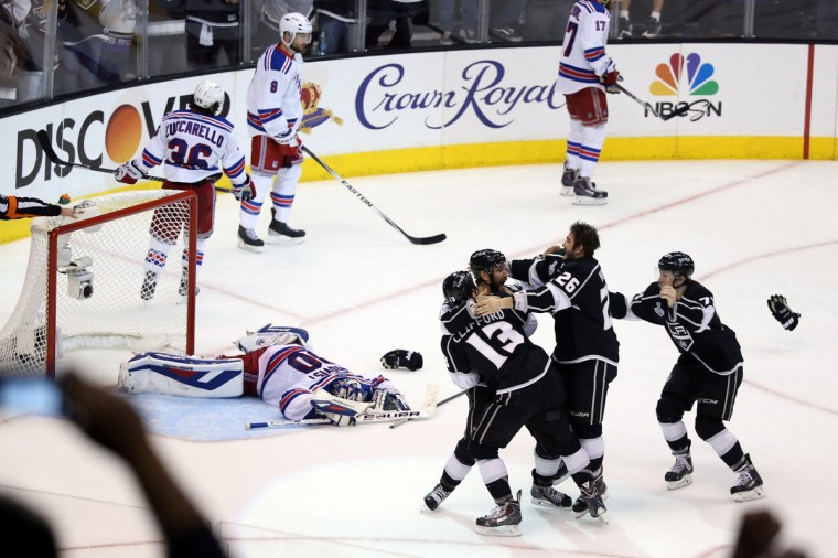 Alec Martinez of the Los Angeles Kings and the Kings celebrate after scoring the game-winning goal in double overtime against the New York Rangers to win 3-2 in Game Five of the 2014 Stanley Cup Final at Staples Center on June 13, 2014 in Los Angeles, California. (Christian Petersen/Getty Images)