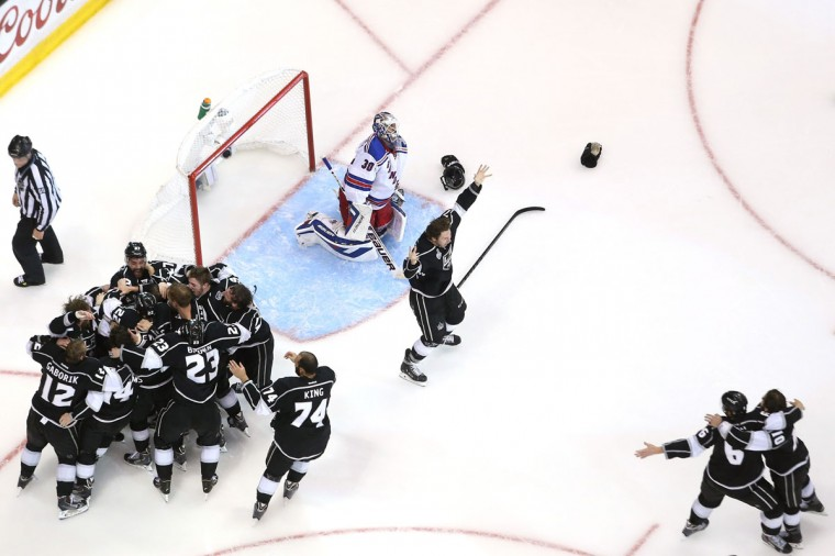 Alec Martinez #27 of the Los Angeles Kings and the Kings celebrate after scoring the game-winning goal in double overtime against goaltender Henrik Lundqvist #30 of the New York Rangers to win 3-2 in Game Five of the 2014 Stanley Cup Final at Staples Center on June 13, 2014 in Los Angeles, California. (Bruce Bennett/Getty Images)