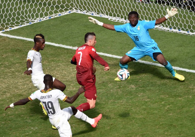 Portugal's forward and captain Cristiano Ronaldo (Center) misses a shot on goal as Ghana's goalkeeper Fatau Dauda (Right) defends during the Group G football match between Portugal and Ghana at the Mane Garrincha National Stadium in Brasilia during the 2014 FIFA World Cup on June 26, 2014. (Evaristo Sa/Getty Images)
