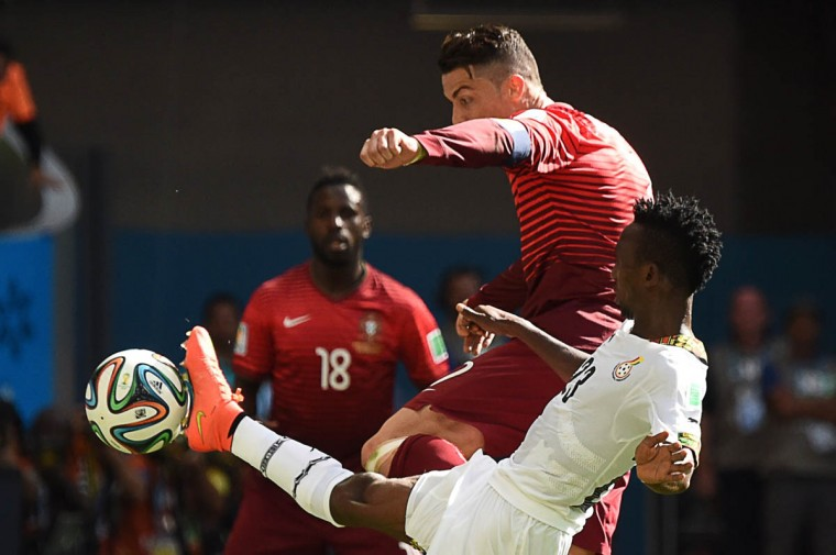 Portugal's forward and captain Cristiano Ronaldo (top) misses a shot on goal as Ghana's defender Harrison Afful defends during the Group G football match between Portugal and Ghana at the Mane Garrincha National Stadium in Brasilia during the 2014 FIFA World Cup on June 26, 2014. (Christophe Simon/Getty Images)