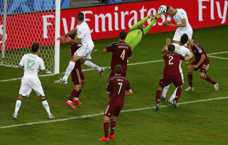 Algeria's Islam Slimani (13) heads to score past Russia's goalkeeper Igor Akinfeev during their 2014 World Cup Group H soccer match at the Baixada arena in Curitiba June 26, 2014. (Amr Abdallah Dalsh/Reuters photo)