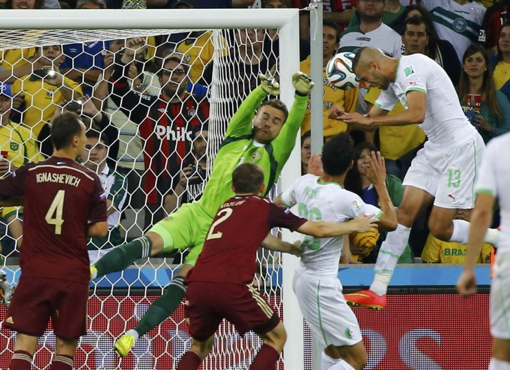 Algeria's Islam Slimani (Right) heads the ball to score a goal against Russia during their 2014 World Cup Group H soccer match at the Baixada arena in Curitiba June 26, 2014. (Damir Sagolj/Reuters photo)